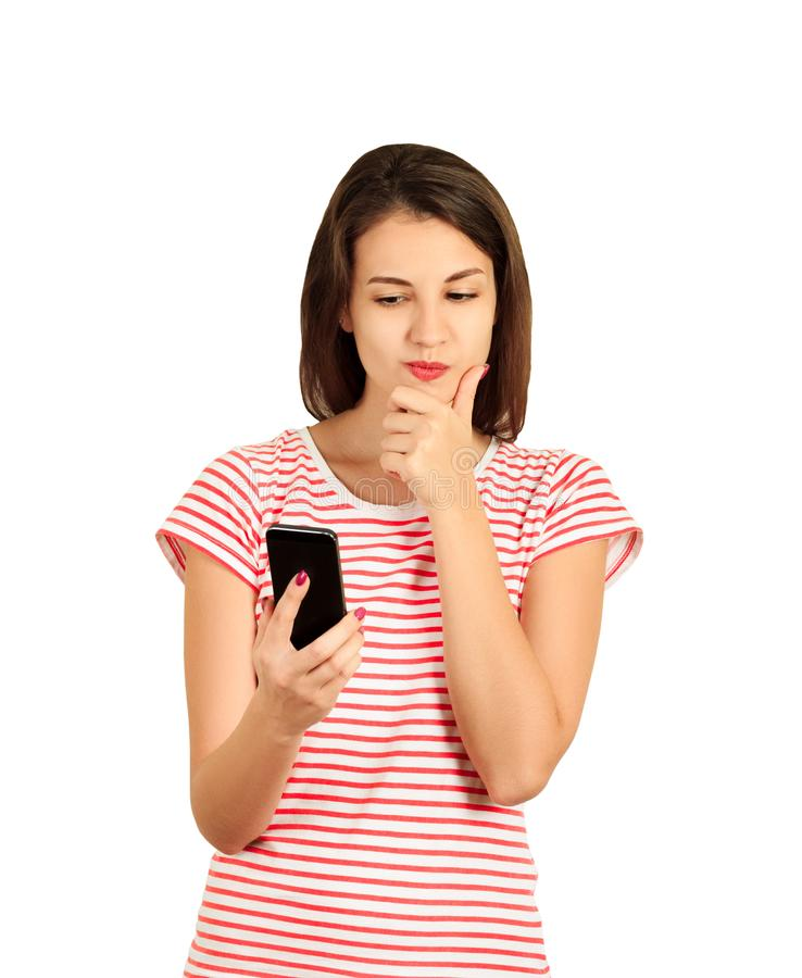 Beautiful thought and thinking woman checking her mobile phone. emotional girl isolated on white background stock photography