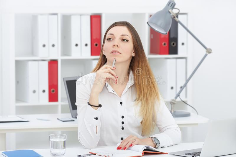 Beautiful thoughtful business woman sitting at office workplace looking into the distance. stock photography