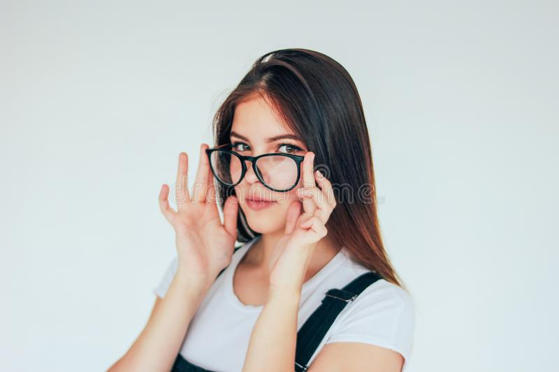 Beautiful thoughtful girl in glasses with dark long hair in white t-shirt isolated on white background stock image