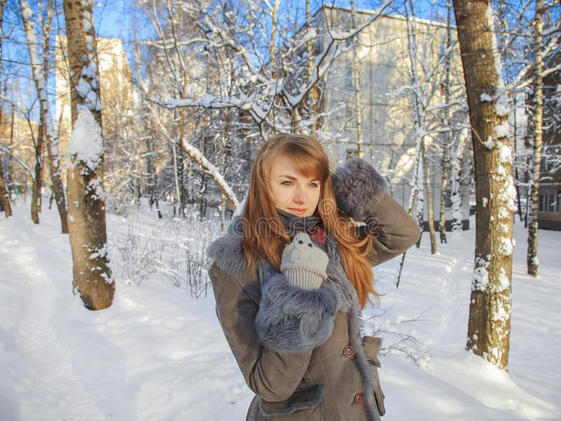 Beautiful thoughtful girl with red hair is on the background of a winter city on a sunny day stock photos