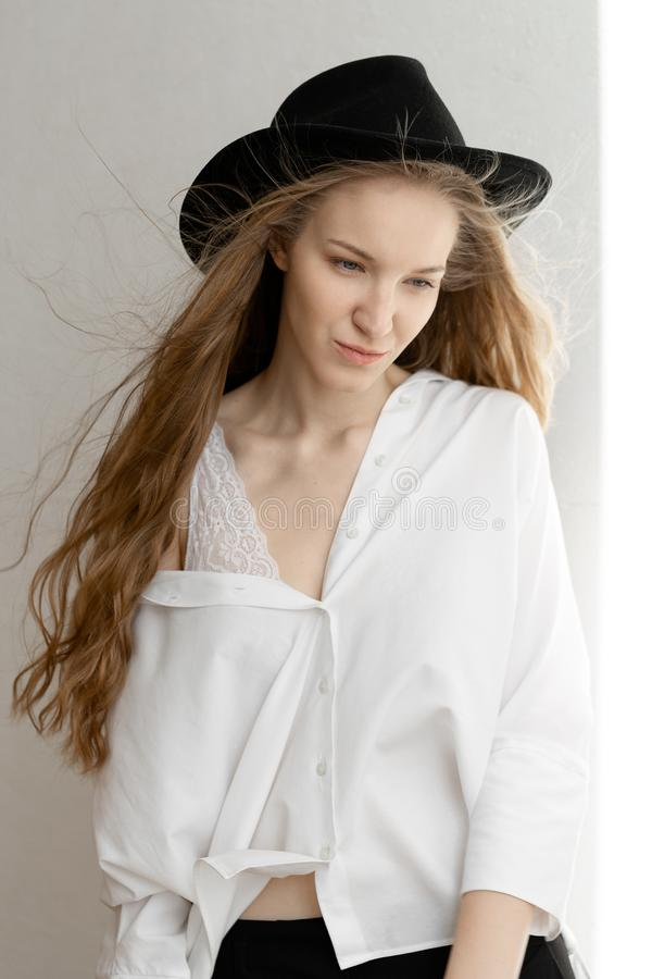 Beautiful thoughtful model looking down in black hat white shirt and black trousers stock photography