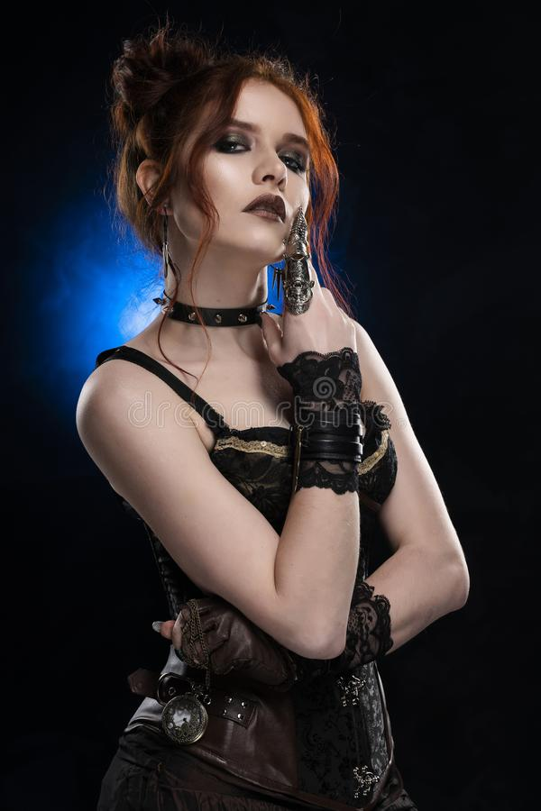 A beautiful thoughtful redhead cosplay girl wearing a Victorian-style steampunk costume with big breasts in a deep neckline. Portrait. Black And blue stock image