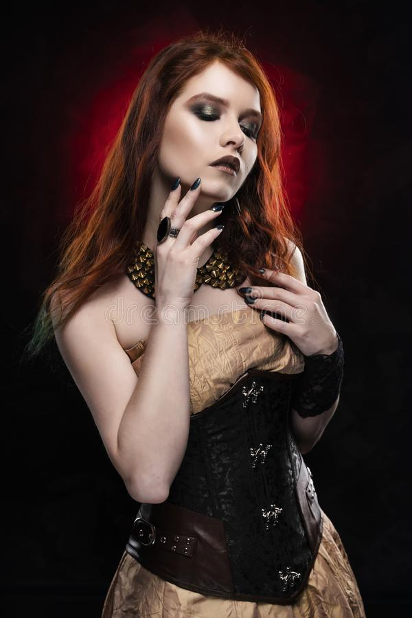 A beautiful thoughtful redhead cosplay girl wearing a Victorian-style steampunk dress and corset. Portrait. Black and red stock photo