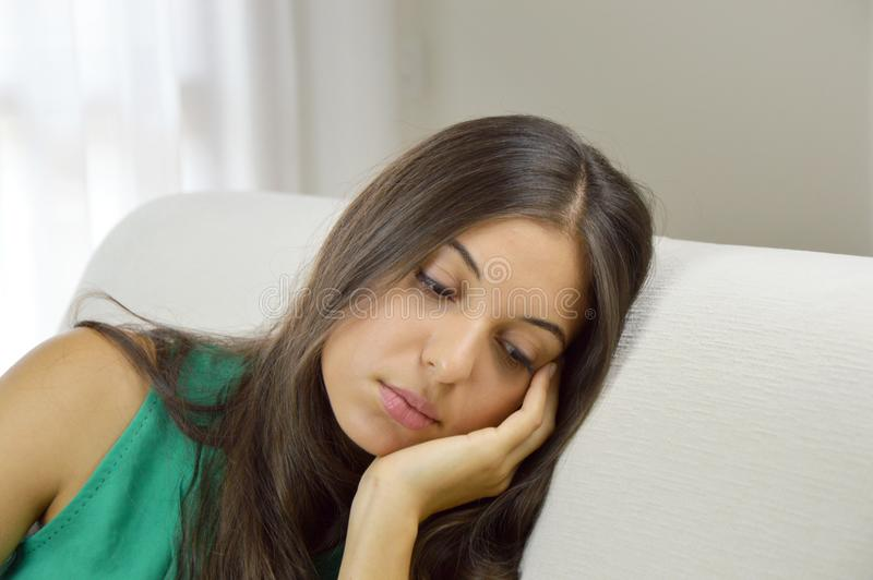 A beautiful thoughtful sad thinking girl with green tank top on sofa.  royalty free stock photos