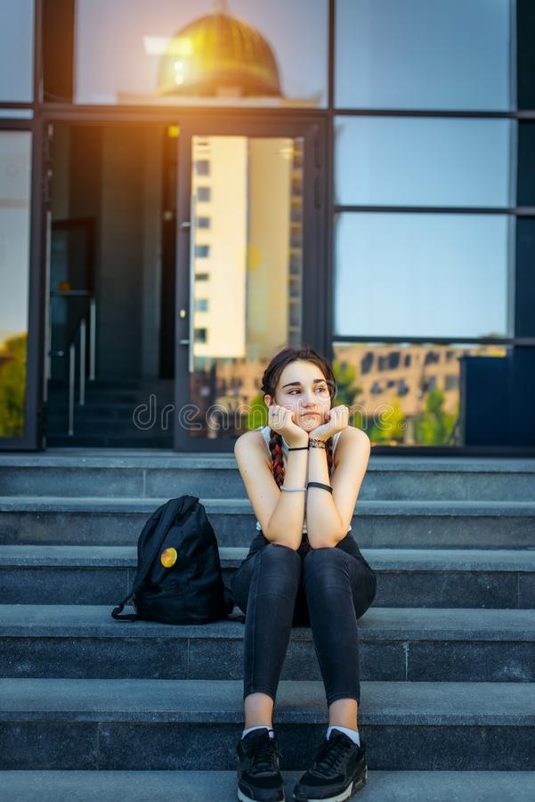 Beautiful thoughtful student sitting on the stairs outdoors in between classes. Student life, the concept of education.  royalty free stock photo