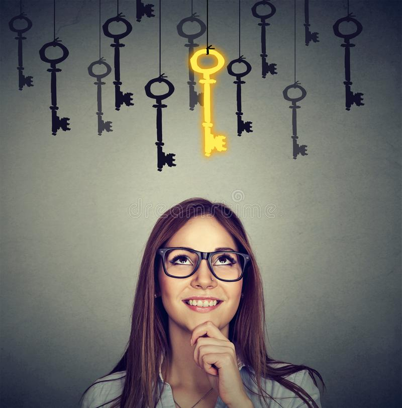 Smiling woman looking up at vintage golden key to success among many others hanging. Beautiful thoughtful woman looking upSmiling woman looking up at vintage royalty free stock images