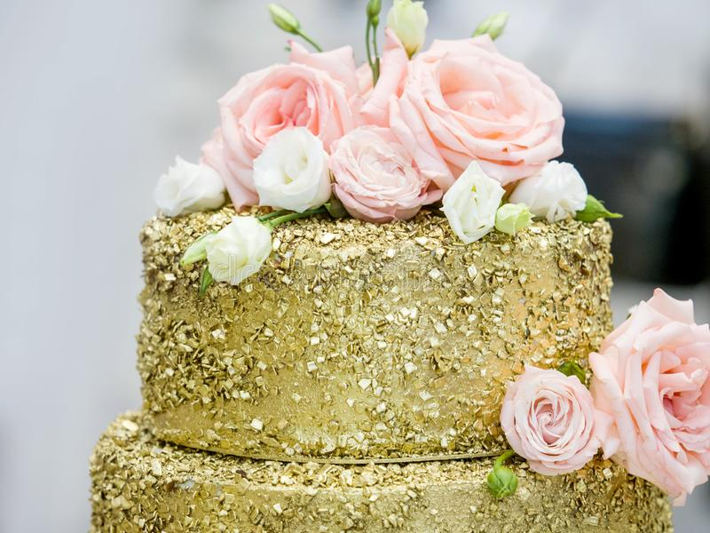 Beautiful three-story golden wedding cake decorated with flowers royalty free stock image