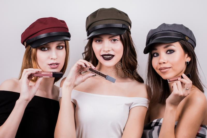 Beautiful three women with makeup and in caps advertise lipstick, lip gloss. Beauty, fashion, fashion, cosmetics products. stock photos