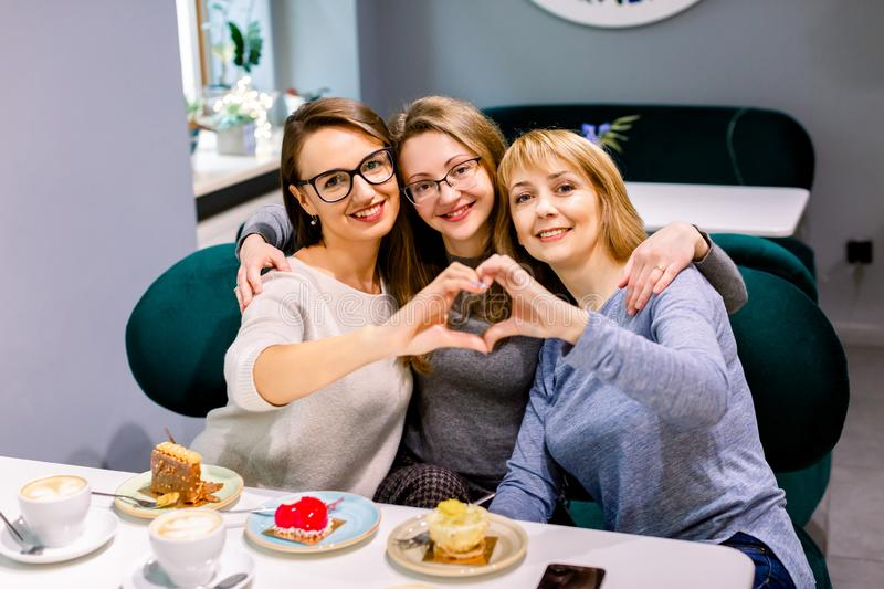 Beautiful three young women drinking a cup of black coffee with delicious desserts, smiling in love showing heart symbol royalty free stock image