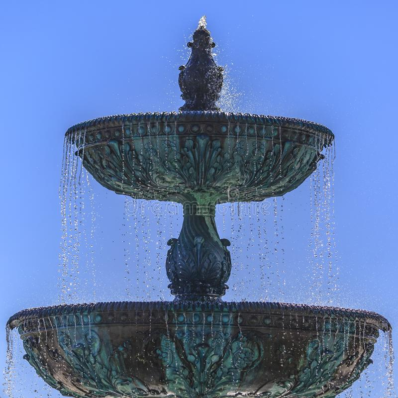 Beautiful tiered fountain with blue sky late day. Beautiful tiered fountain against blue sky. Two tiered blue and gray fountain with intricate design against a royalty free stock photo