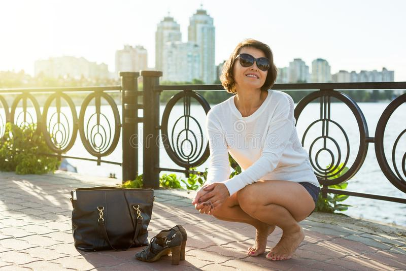 Beautiful, tired barefooted woman. City style, the end of the wo royalty free stock photography