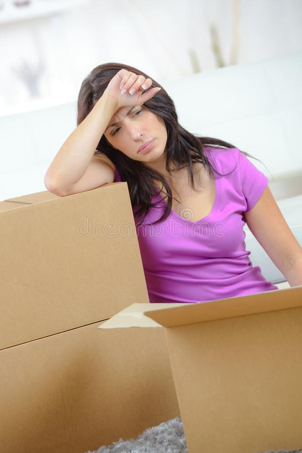 Beautiful tired woman on floor near moving boxes stock images