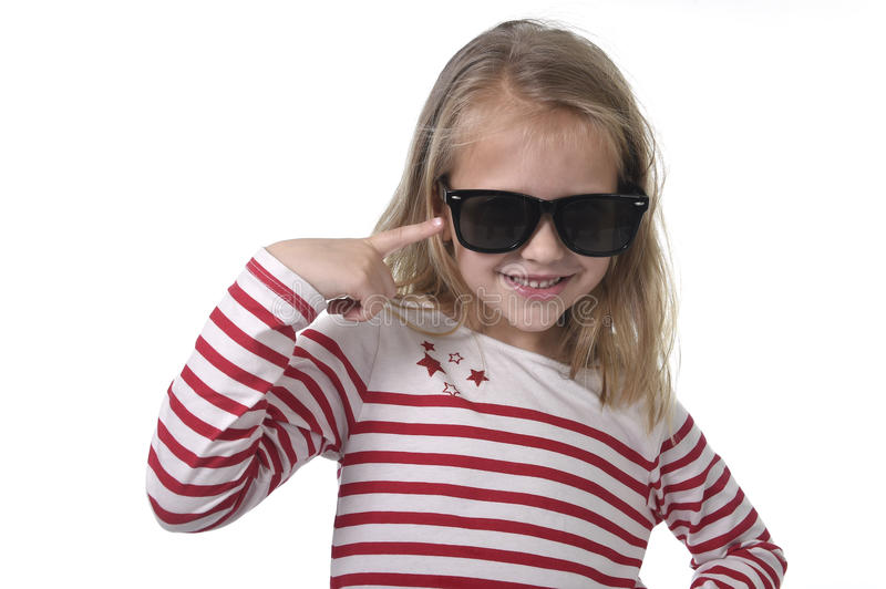 Beautiful 6 to 8 years old female child with blond hair wearing big sunglasses smiling happy and playful royalty free stock photography