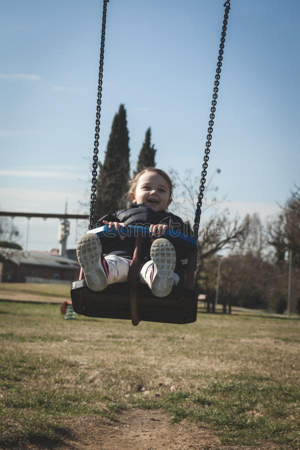 Toddler girl having fun on a swing stock images