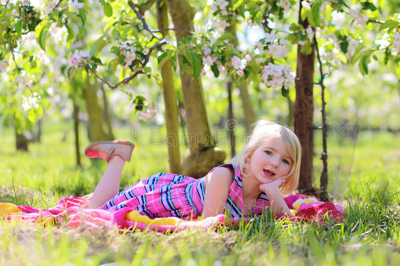 Beautiful toddler girl playing in blossoming fruit orhcard royalty free stock photography