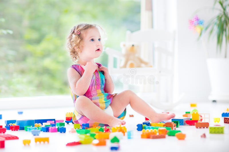Beautiful toddler girl sitting on a floor in a toy mess royalty free stock image