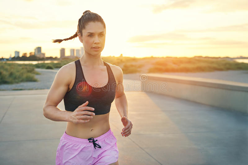 Beautiful and toned female jogger running. Beautiful and toned female jogger with swinging ponytail and pink shorts running in city park during sunrise. Includes stock photos