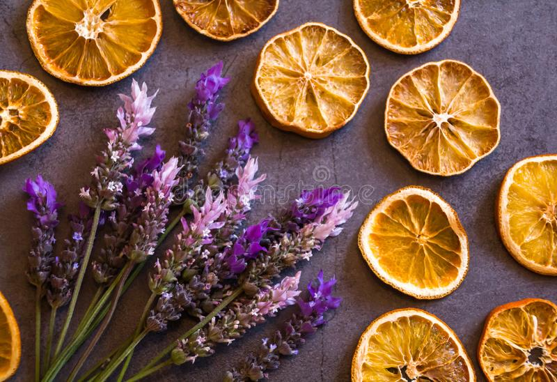 Beautiful top view flat lay arrangement of dry Oranges and purple and pink lavender flowers bouquet on dark grey background royalty free stock image