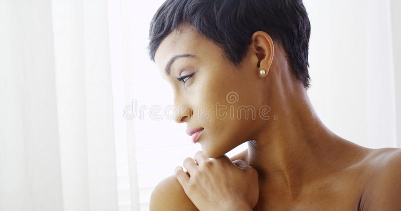 Beautiful topless black woman hugging herself and looking out window. At home stock images
