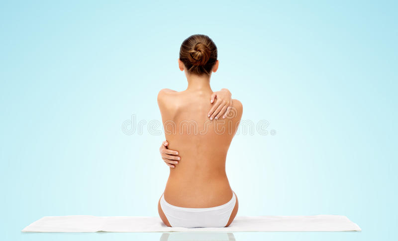 Beautiful topless young woman on towel from back stock images