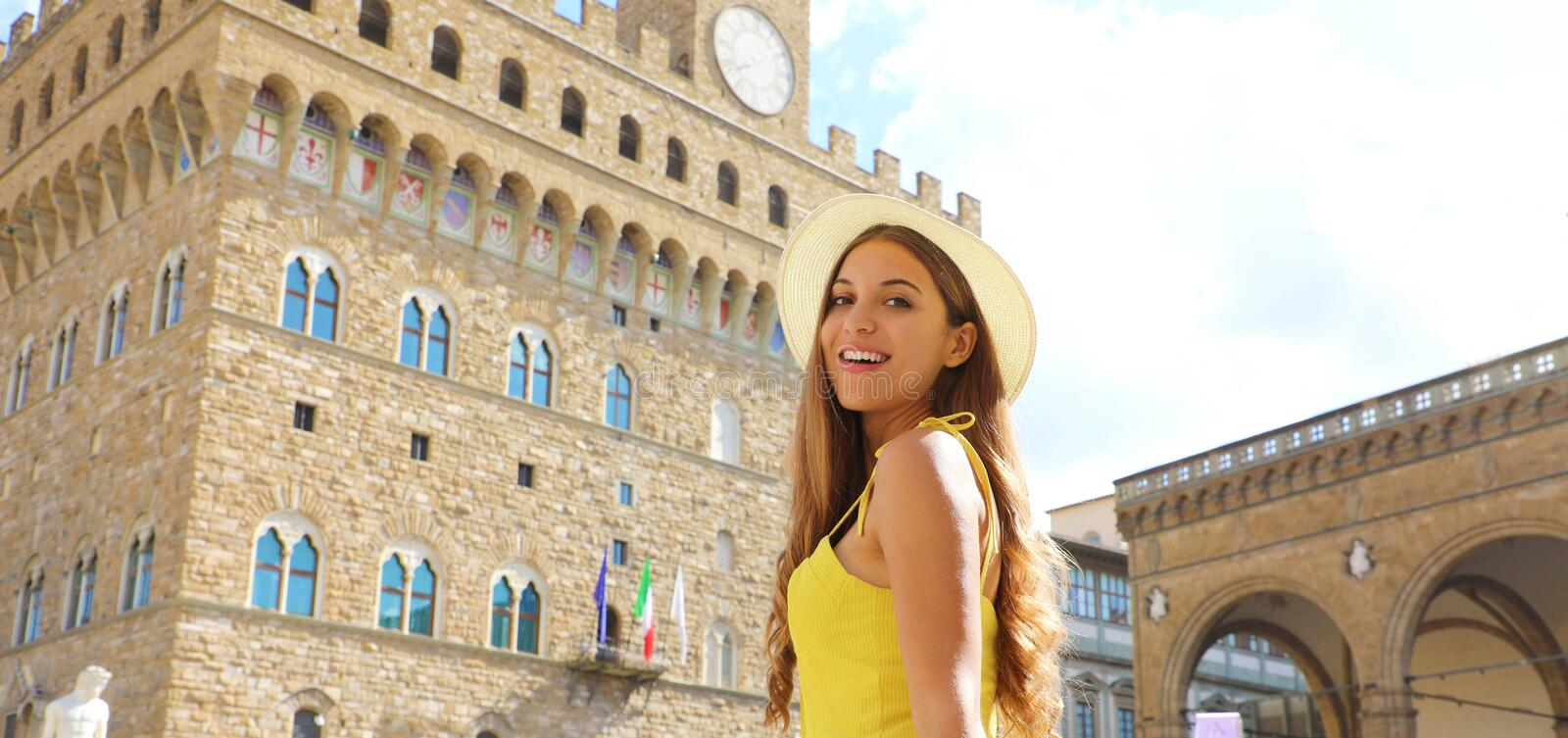 Beautiful tourist girl in Florence with Palazzo Vecchio palace  on the background. Panoramic banner view of young woman in her stock photo
