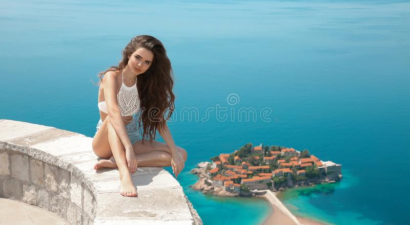 Beautiful tourist sightseeing Sveti Stefan island in Budva, Mont. Enegro. brunette traveller girl visiting Adriatic Sea, Balkans. Summer travel vacation royalty free stock photos