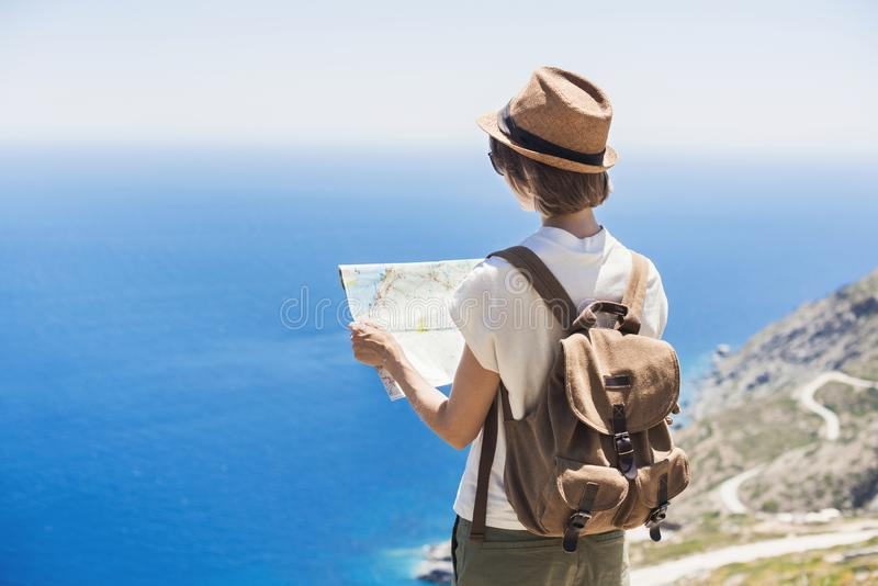Beautiful tourist woman with backpack holding map. Traveler girl looking for hiking route with sea and mountain at background. royalty free stock image
