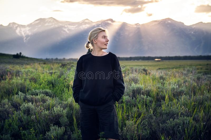 Beautiful tourist woman traveling and enjoy the nature mountain view in green field on a summertime vacation in Yellowstone Nation stock images