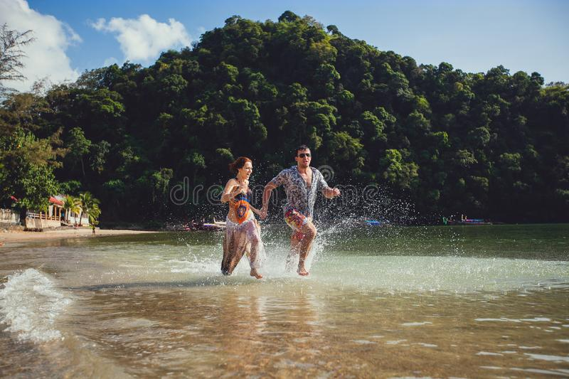 Beautiful tourist young couple holding hands together running along the beach shore with mountains and blue sea water and sky, royalty free stock images