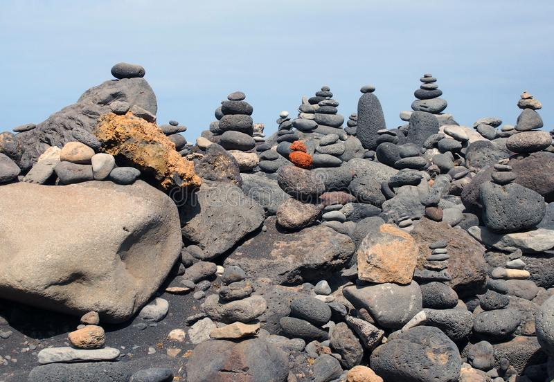 Beautiful towers of stacked pebbles and stones in a large arrangement on a black sand beach with blue sky royalty free stock photo