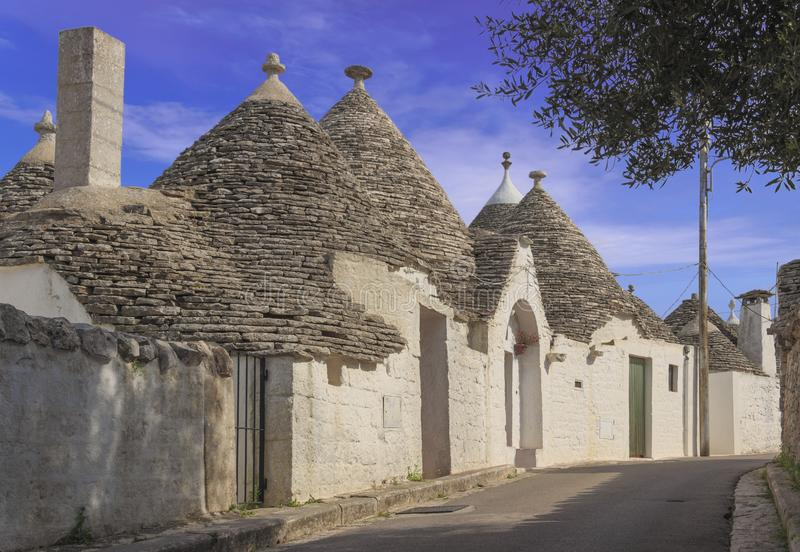 Beautiful town of Alberobello with trulli houses among green plants and flowers, main touristic district, Apulia, Italy. stock photos