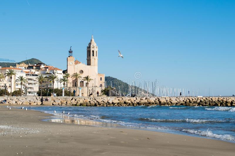 The beautiful town of Sitges with seagulls, Landscape of the coastline in Sitges, Parròquia de Sant Bartomeu i Santa. The beautiful town of Sitges with royalty free stock image