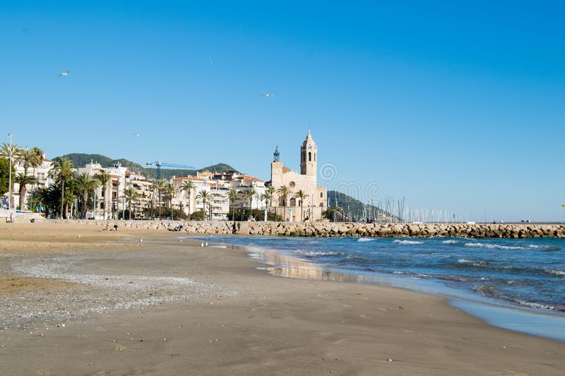 The beautiful town of Sitges with seagulls, Landscape of the coastline in Sitges, Parròquia de Sant Bartomeu i Santa. The beautiful town of Sitges with stock image