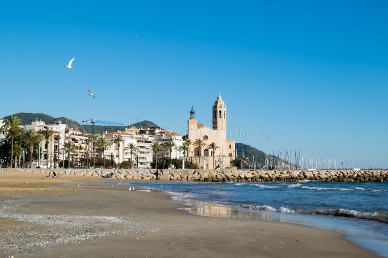 The beautiful town of Sitges with seagulls, Landscape of the coastline in Sitges, Parròquia de Sant Bartomeu i Santa. The beautiful town of Sitges with stock images