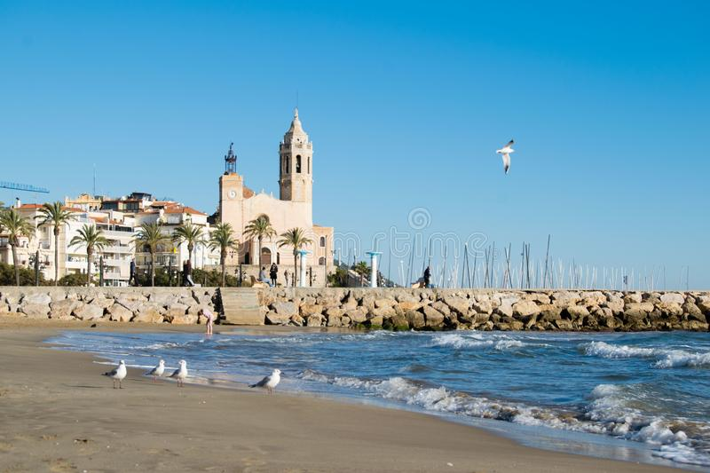 The beautiful town of Sitges with seagulls, Landscape of the coastline in Sitges, Parròquia de Sant Bartomeu i Santa. The beautiful town of Sitges with royalty free stock photography