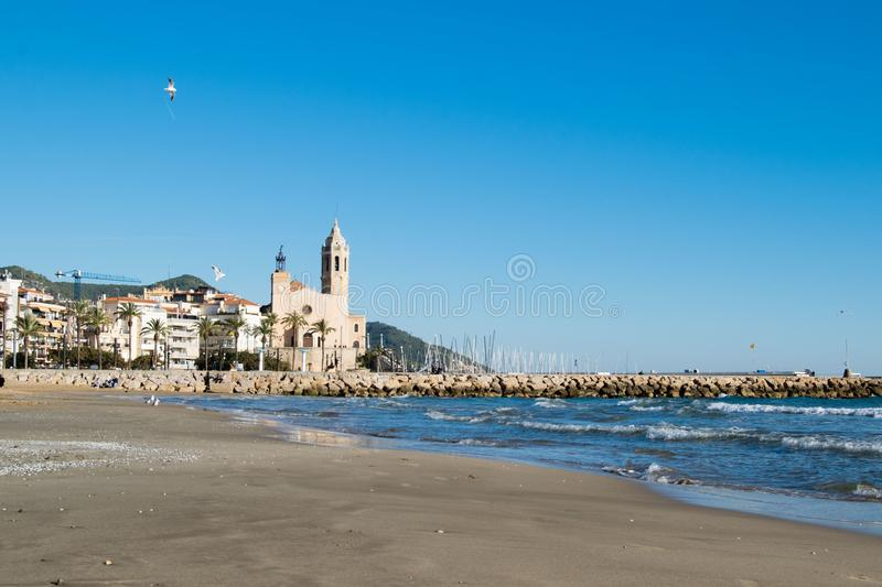 The beautiful town of Sitges with seagulls, Landscape of the coastline in Sitges, Parròquia de Sant Bartomeu i Santa. The beautiful town of Sitges with stock photos