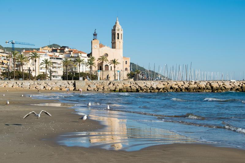 The beautiful town of Sitges with seagulls, Landscape of the coastline in Sitges, Parròquia de Sant Bartomeu i Santa. The beautiful town of Sitges with stock photography