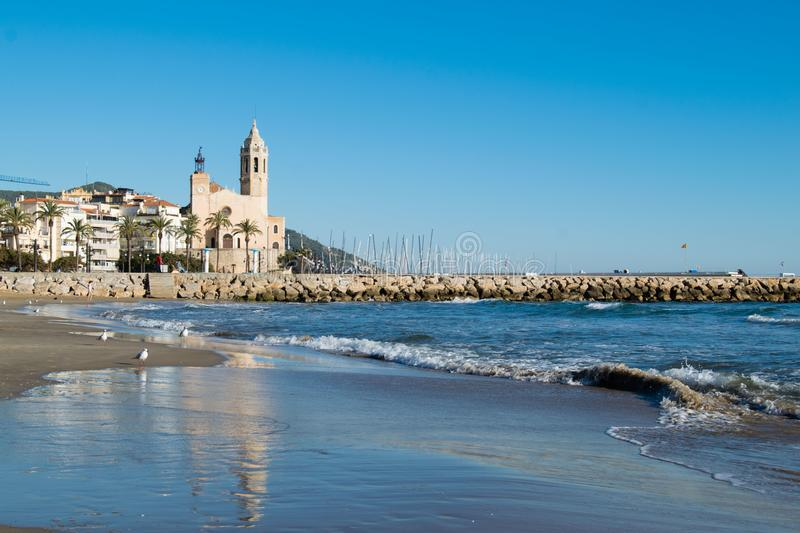 The beautiful town of Sitges with seagulls, Landscape of the coastline in Sitges, Parròquia de Sant Bartomeu i Santa. The beautiful town of Sitges with royalty free stock photo