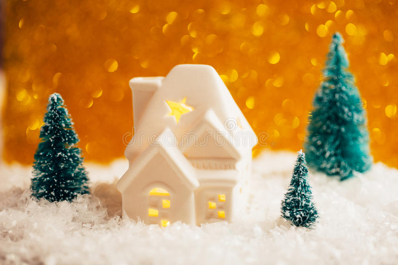 Beautiful toy christmas card. Beautiful christmas card. Little house with windows and light inside and three pines are standing in toy snowy forest on sparkling royalty free stock images