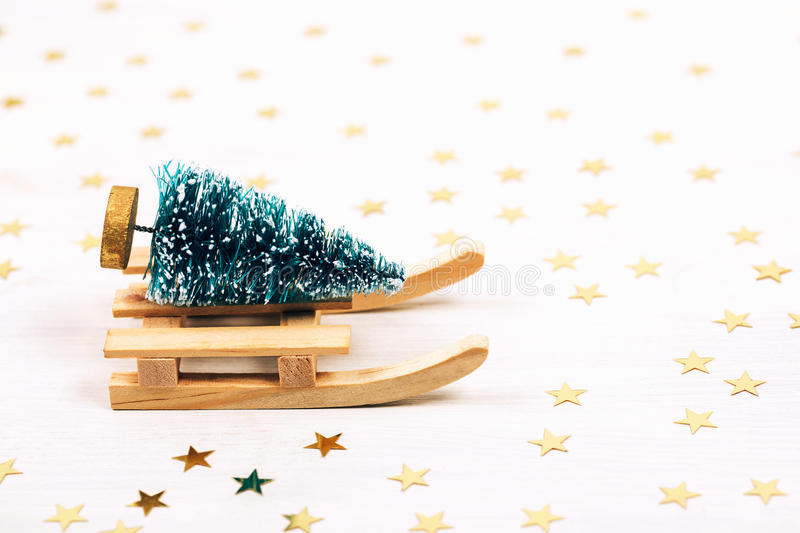 Beautiful toy christmas card. Beautiful christmas card. Little toy pine on wooden sleigh on sparkling background stock photography