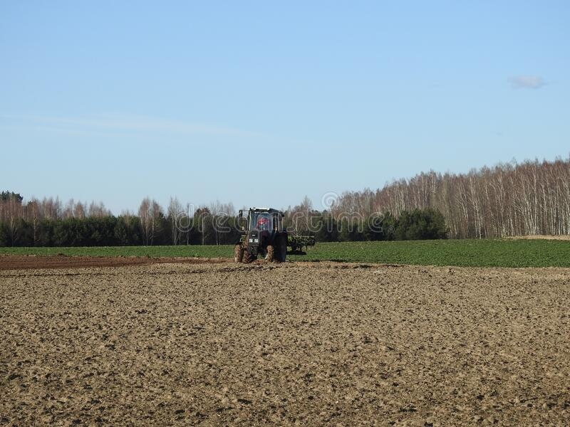 Beautiful tractor working in spring, Lithuania stock photo