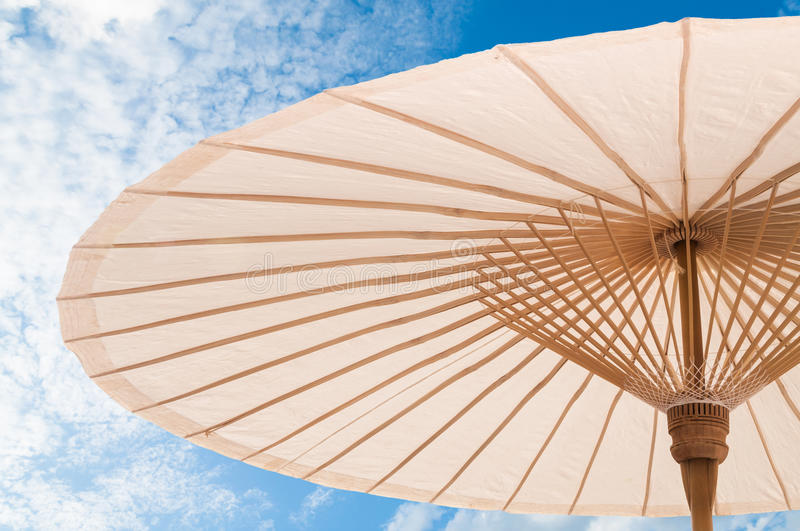 Beautiful Traditional Asian paper and bamboo umbrella. With a rounded handle on blue sky stock photo