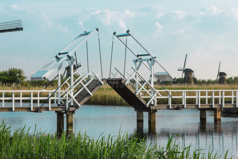Beautiful traditional dutch windmills near the water channels with drawbridge royalty free stock photography
