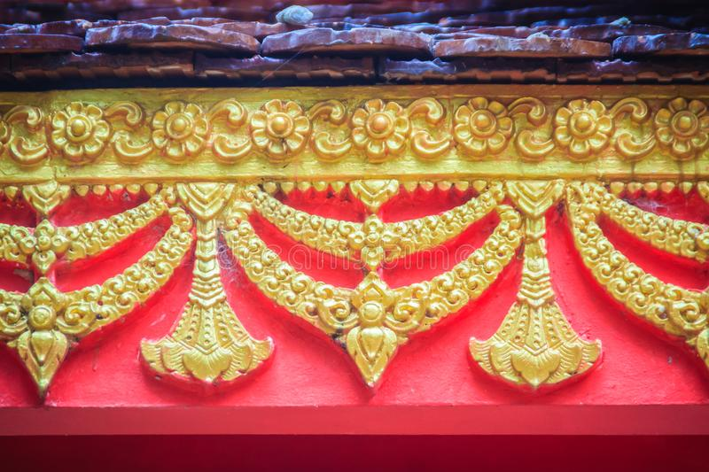 Beautiful traditional golden Thai style stucco patterned for decorative on wall background at Buddhist temple in Thailand. stock photo