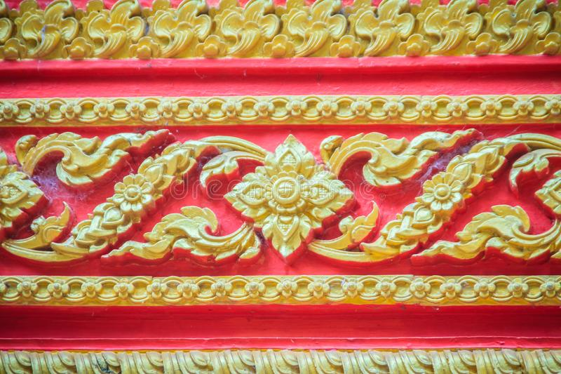 Beautiful traditional golden Thai style stucco patterned for decorative on wall background at Buddhist temple in Thailand. royalty free stock photography