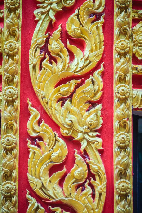 Beautiful traditional golden Thai style stucco patterned for decorative on wall background at Buddhist temple in Thailand. royalty free stock photo