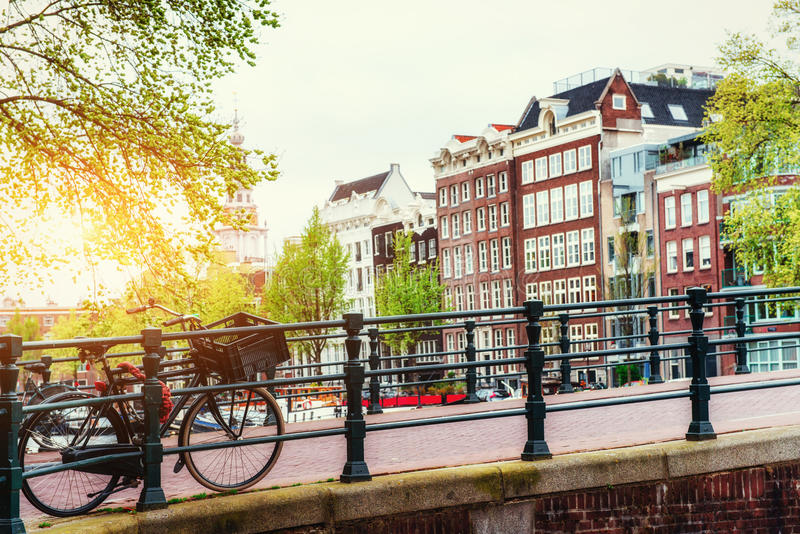 Beautiful tranquil scene of the city Amsterdam. Beautiful tranquil scene of the city of Amsterdam. Bicycles along the street on the bridge over the canal royalty free stock photos