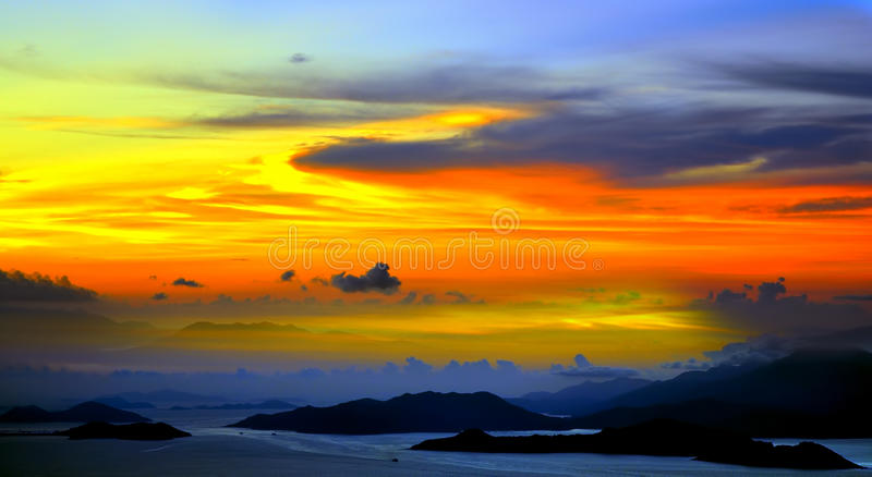 Beautiful tranquil sunset. Over the ocean with silhouetted clouds and mountain range royalty free stock image