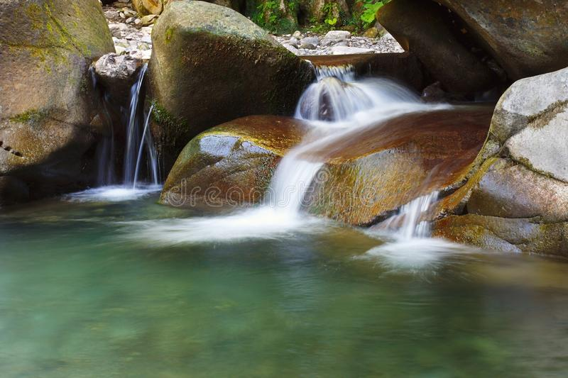 Beautiful tranquil waterfall among the rocks of mountain creek royalty free stock images