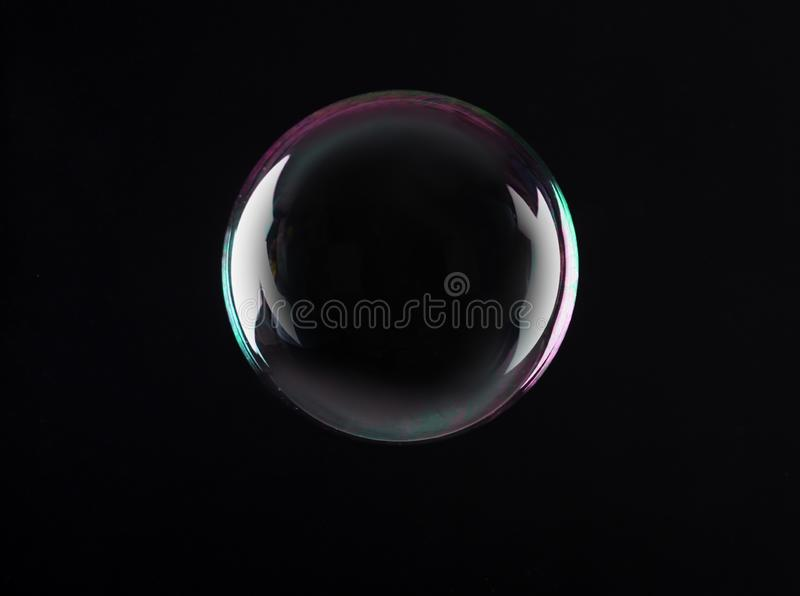 Beautiful translucent soap bubble on dark background. Space for text royalty free stock photo
